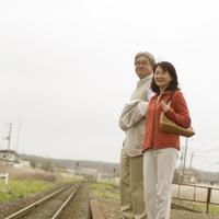 ローカルな駅のホームで電車を待つシニア夫婦