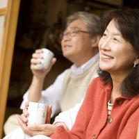 古い日本家屋で庭の眺めを楽しむシニア夫婦