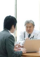 製品を売り込む製薬会社の営業マンと話を聞く医者