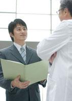 製品を売り込む製薬会社の営業マンと話を聞く医者 20027004173| 写真素材・ストックフォト・画像・イラスト素材|アマナイメージズ