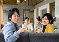 カフェで微笑む20代のカップルと2人の女性