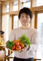カフェの窓辺で野菜を持ち微笑む30代の男性