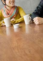 カフェでコーヒーを飲む20代のカップルの手元