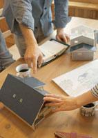 住宅模型を指差し打合せをする建築士とデザイナーの手元