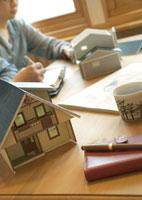 住宅模型のある机で打合せをする建築士とデザイナー