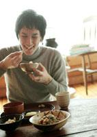 笑顔で和食の朝食を食べる20代の男性