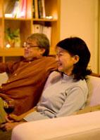 リビングのソファーに座りテレビを見るシニア夫婦