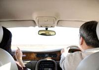 車の運転をする男性と助手席に座る女性の後姿