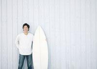 サーフボードを持ち微笑む20代の男性