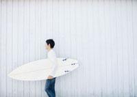 サーフボードを持ち歩く20代の男性