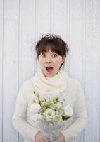 ブーケを持ち驚いた顔をする20代女性のウェディングイメージ 20027004724| 写真素材・ストックフォト・画像・イラスト素材|アマナイメージズ