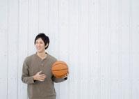 バスケットボールを持ち微笑む20代の男性