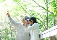 森林の木道で写真を撮るシニア夫婦