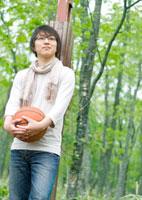 公園でバスケットボールを持ち遠くを見る20代の男性