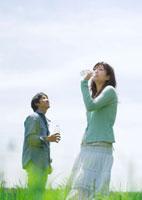 草原で水を飲む20代の男女
