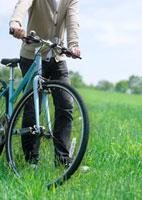 草原で自転車を押して歩く20代の男性