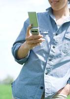 草原に立ち携帯電話でメールをする20代の男性