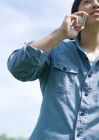 草原に立ち携帯電話で話をする20代の男性