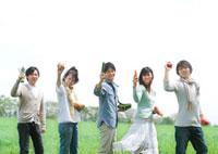 草原で野菜を持ち微笑む5人の若者たち