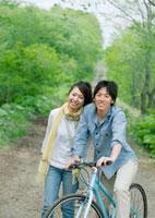 一本道で自転車に乗る男性と隣で微笑む女性