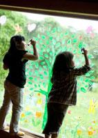 ガラスの窓に木の絵を描く2人の女の子の後姿