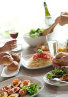 テーブルの上のパーティー料理と4人の若者たちの手元