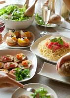 パーティー料理と食事をする若者たちの手元