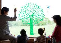 ガラスの窓にエコをイメージした木の絵を描く4人家族の後姿
