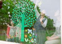 ガラスの窓にエコをイメージした木の絵を描く4人家族