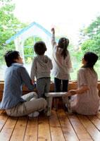 ガラスの窓に家の絵を描く4人家族の後姿