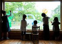 ガラスの窓に絵を描く5人の子供たちの後姿