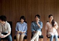 椅子に座りそれぞれ別の動作をする4人の若者たち