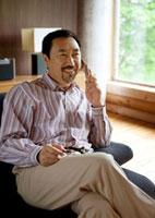 ソファーに座り携帯電話で話すシニア男性