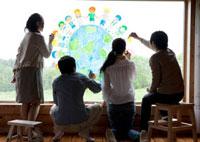 ガラス窓に地球と子供たちの絵を描く4人若者たちの後姿