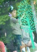 ガラスの窓にエコをイメージした木の絵を描く家族