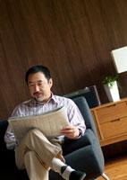 ソファーに座り新聞を読むシニア男性