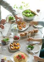 テーブルの上のパーティー料理と4人の若者たちの手元 20027004909| 写真素材・ストックフォト・画像・イラスト素材|アマナイメージズ