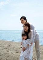 海辺で女の子を抱き締める両親