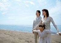 海辺で女の子と手をつなぐ母親と父親