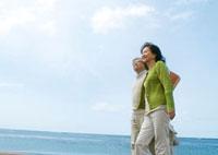 海辺を散歩するシニア夫婦
