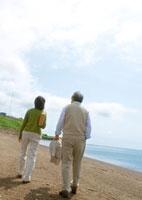 海辺を散歩するシニア夫婦の後姿
