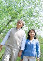 新緑の中を散歩するシニア夫婦