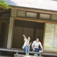 和室の縁側に座り庭園を眺める若いカップル