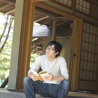 和室の縁側に座り本を読む若い男性