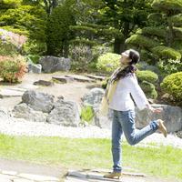 日本庭園でとび跳ねる若い女性