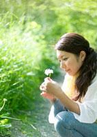 新緑の下で野花を摘んだ若い女性