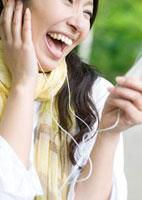 新緑の下で音楽を聴く若い女性