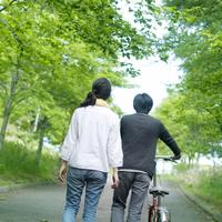 新緑の下で自転車を押しながら歩く若いカップルの後ろ姿