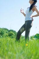 自然の中でペットボトルの水を持ち微笑む健康的な20代の女性