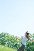自然の中でペットボトルの水を持ち走る健康的な20代の女性